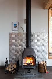 A metal panel protects the wall behind a wood-burning stove and adds a  visual