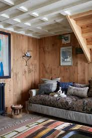 a large painting by irish artist martin finnin hangs in the living room of a tiny barn decorated by antiques dealer and designer christopher howe
