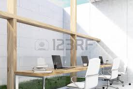 Long Office Table Is Standing Near A White Brick Wall On Patch Of Grass.
