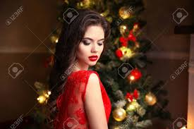 beauty makeup elegant brunette woman portrait in red dress over tree lights background
