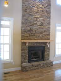 floor to ceiling stacked stone fireplace ideas with wooden floating shelf