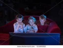 kids watching tv at night. at home by night, three scared kids watching tv night h