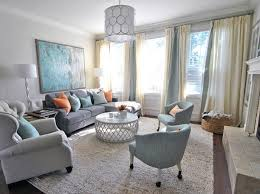 subdued blues and oranges in accents like throw pillows make a room with gray walls a conversation piece