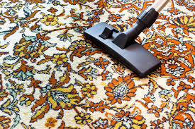 cleaning old carpet with a vacuum cleaner with a black nozzle