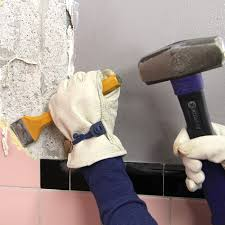 use a hammer and chisel to break off the old tile sometimes you have to smash one tile so you can get the chisel under the others breaking the grout lines