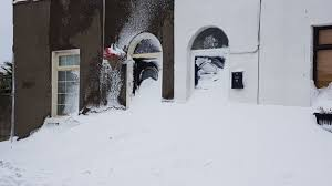 houses in inchicore south dublin with their front doors blocked by drifting snow