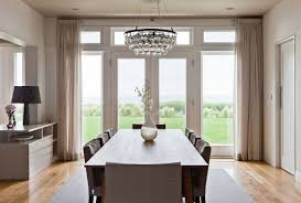 beautiful ochre arctic pear chandelier above teardrop vase and slipcovered dining chairs for contemporary dining room with glass doors and hardwood floors
