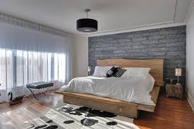 Example of a trendy master medium tone wood floor bedroom design in  Montreal with gray walls
