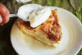 apple pie slice with whipped cream.  With Spooning Whipped Cream Onto A Slice Of Sour Apple Pie To With I