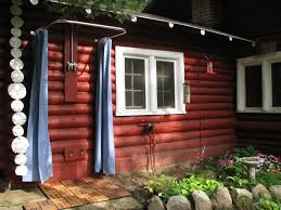inspiring vintage log cabin backyard views with blue sliding shower curtain hang on rounded pipe bars for outside shower decors landscaping ideas