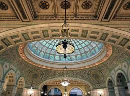 looking up at a colorful tiffany stained glass dome in an ornate room at the