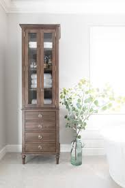 the restoration hardware maison tall bath cabinet graces a bathroom with a distressed rustic storage unit
