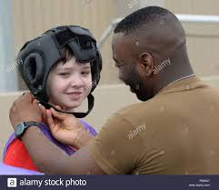 U.S. Navy Petty Officer 1st Class Aaron Gaskins, secures headgear to a  child during the Joint Senior Enlisted Leader Fun Field Day event at Camp  Lemonnier, Djibouti, April 29, 2016. During the