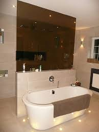 highlight lighting. atmospheric floor lighting and spotlights have been used to highlight the features in this luxury bathroom i
