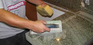 using a rubber float and sponge to apply grout to tile