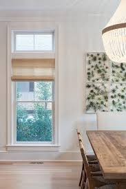 ro sham beaux orbit clear chandelier illuminates a salvaged wood dining table lined with natural owven dining chairs placed before a wall clad in botanical
