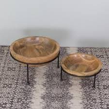 a smooth carved mango wood bowl floats on an iron ring and tripod base the
