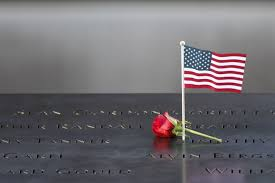 eleven years later remembering sept  a flower and an american flag are placed next to the s inscribed on the edge
