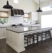 fantastic kitchen features a vaulted ceiling accented with vintage black barn pendants illuminating a white center island topped with gray limestone fitted