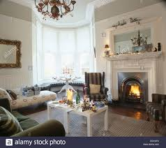 Wing Chairs For Living Room Grey Striped Wing Chair Beside Fireplace Below White Mirror In