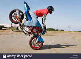stunt bike rider making stoppie stock photo royalty free image