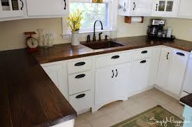 white cabinets and island in small kitchen dark wooden countertop undermount sink coffee maker flower vase kitchen scales