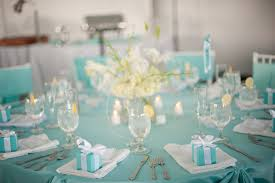 blue wedding decorations ceremony withlarge round table and white flower table centerpieces also wooden chairs