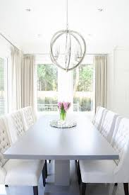 gray pedestal dining table with white tufted dining chairs
