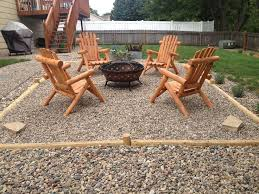pea gravel fire pit with landscape timbers and cedar log adirondack