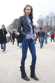 an edgy biker chic lady is on the streets we see this woman wearing a black moto jacket styled with pale white top styled with knee ripped slim jeans