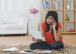 womansortingbillsoncellphone uniquelyindia 56a1dedd3df78cf7726f5ea8