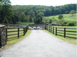 automated wood gate with post and rail fencing on a farm property