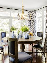 round dining table and black french dining chairs with double twist large chandelier