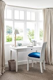Bedroom work space boasts a bay window dressed in natural linen French  pleat drapery panels filled with a white french desk and a white wicker  chair adorned ...