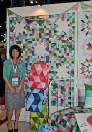 Quilt Market: Spotlight on Fabric Designers & Vanessa Christenson Smiling in Front of Beautiful Quilt Adamdwight.com