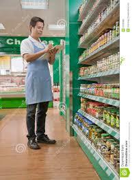 s clerk checking merchandise in supermarket royalty stock s clerk checking merchandise in supermarket