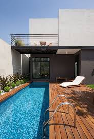 a modern wooden deck with a narrow pool and desert plants lining it