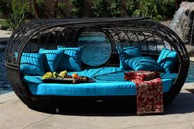 unique patio wicker furniture resin rattan daybed outdoor daybed black finish weather resistant blue seating cushion red floral quilt poolside furniture stone slab flooring