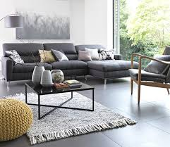 large grey corner sofa in living room area with ter cushions and yellow knitted footstool