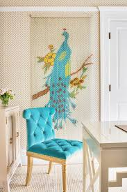 contemporary sitting space with pop of blue on tufted chair and tropical peacock wall decor over textured carpet