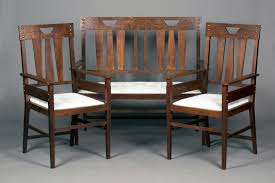 an early 20th century arts and crafts oak three piece suite comprising a settee and a pair of armch