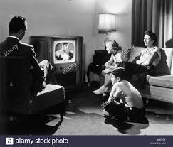 black kids watching tv. 1950s family in living room watching television - stock image black kids watching tv