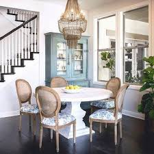 round whitewashed dining table with gray beaded chandelier