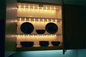 lighting for shelves. shelf lighting is attached to tops of shelves in cabinet for b