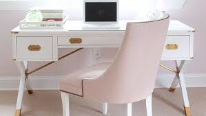 chic office space features a white campaign desk accented with brass hardware paired with a blush pink chair