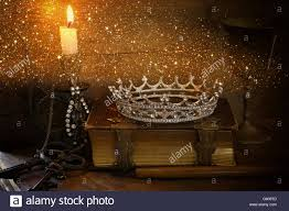 low key image of beautiful diamond queen crown on old book burning candle vine filtered with glitter overlay fantasy middl