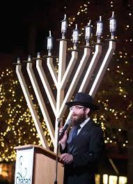 rabbi mendel blecher with chabad of the woodlands addresses worshipers during a menorah lighting