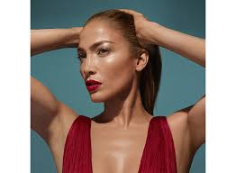 jlo glow makeup jennifer lopez poses with her hands on her hair staring off