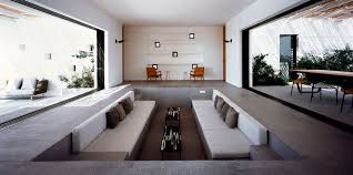 the sunken living room has a set of small stairs in opposite corners to make it easy to walk down into the recessed lounging area that has two long