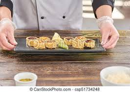 Sushi Cook Chef Hands Holding Plate With Sushi Rolls
